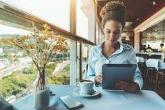 Gril afroamericano en barra con la tableta y el café digitales Fotografía de archivo