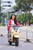 Gril bonito em uma e-bicicleta retro vermelha do estilo, Kunming, China Fotografia de Stock Royalty Free