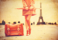 Gril in coat with umbrella and suitcase Royalty Free Stock Photos