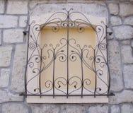 Gril décoratif de fer travaillé sur la fenêtre murée Image stock