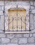Gril décoratif de fer travaillé sur la fenêtre murée Images stock