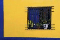 Gril d'hublot de fer travaillé dans le mur jaune lumineux avec la trame bleue Photos stock