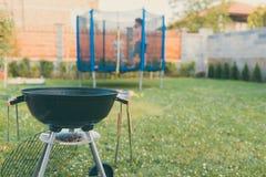 Gril de barbecue de BBQ de charbon de bois de bouilloire dans le jardin ou l'arrière-cour Trempoline extérieur brouillé à l'arriè image libre de droits