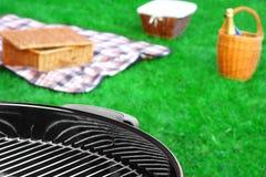 Gril de BBQ, panier de pique-nique avec du vin, couverture sur la pelouse Images stock