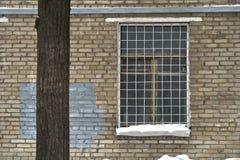 Gril de fenêtre sur une fenêtre de vieille maison soviétique de brique Images libres de droits