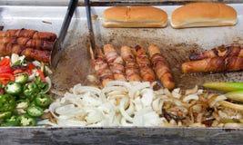 Gril de marchand ambulant avec les hot-dogs et les oignons Photographie stock libre de droits