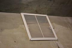 Gril de ventilation dans l'appartement sans finissage murs en béton avec la grille d'aération blanche images libres de droits