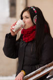Gril drinking coffee in iwinter Stock Image