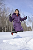 A gril jump happily. In snow Royalty Free Stock Photo