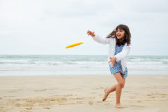 Gril playing frisbee. Girl running to catch the flying frisbee disc on the beach in a cloudy day Royalty Free Stock Image