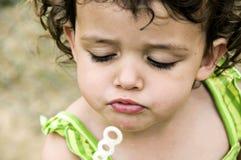 Gril que intenta soplar burbujas Imagen de archivo libre de regalías