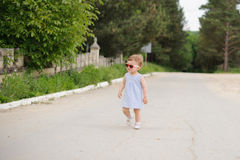 Gril on Road. Girl in sunglasses walking on road Stock Photo