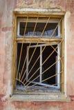 Gril rouillé de sécurité de fer sur la fenêtre cassée dans la vieille brique ruinée Photo stock