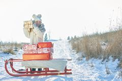 Gril with sled full of presents. Shakes gift box in winter Royalty Free Stock Photography
