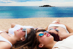 Grilfriends relaxing together on Carribean beach. Portrait of Cute teen girlfriends laying with heads together on Carribean beach Stock Image