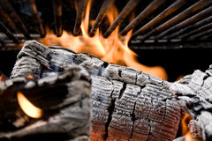 Grill. Burning log heating a grill Royalty Free Stock Images
