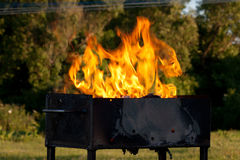 Grill. Orange flames leaping over an open empty grill outdoors Stock Photo