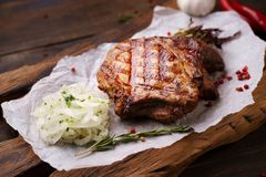 Grill and barbeque, ribeye steak, meat restaurant. Grill and barbeque, meat restaurant menu, juicy medium rare ribeye steak served with marinated onion on board stock photo