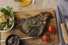 Grill beef steak on bones with potatoes and tomatoes on a board t-bone. A Stock Photography