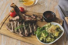 Grill beef steak on bones with potatoes and tomatoes on a board t-bone. A Royalty Free Stock Photography