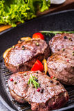 Grill beef steak. Portions thick beef juicy sirloin steaks on grill teflon pan or old wooden board Stock Photos