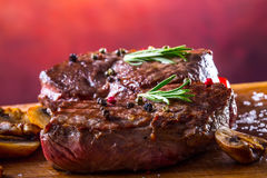 Grill beef steak. Portions thick beef juicy sirloin steaks on grill teflon pan or old wooden board Royalty Free Stock Photography