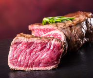 Grill beef steak. Portions thick beef juicy sirloin steaks on grill teflon pan or old wooden board.  Royalty Free Stock Photos