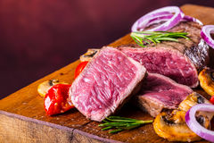 Grill beef steak. Portions thick beef juicy sirloin steaks on grill teflon pan or old wooden board Stock Photography