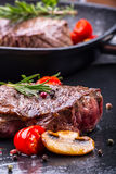 Grill beef steak. Portions thick beef juicy sirloin steaks on grill teflon pan or old wooden board Royalty Free Stock Images
