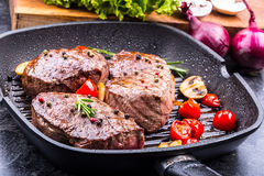 Grill beef steak. Portions thick beef juicy sirloin steaks on grill teflon pan or old wooden board Stock Image