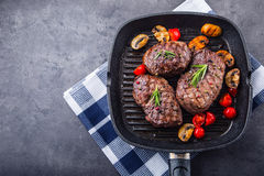 Grill beef steak. Portions thick beef juicy sirloin steaks on grill teflon pan or old wooden board.  Royalty Free Stock Photography