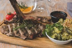 Grill beef steak  with potatoes and tomatoes on a board. A Royalty Free Stock Images