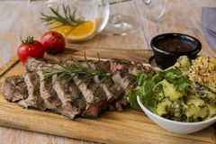 Grill beef steak  with potatoes and tomatoes on a board. A Royalty Free Stock Photography