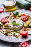 Grill Brie camembert cheese zucchini with chili pepper and olive oil. Italian mediterranean or greek cuisine. Royalty Free Stock Photo