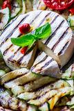 Grill Brie camembert cheese zucchini with chili pepper and olive oil. Italian mediterranean or greek cuisine. Royalty Free Stock Image