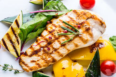 Grill chicken breast. Grilled vegetables with chicken breast. Grilled chicken with vegetables on oak table stock photography