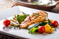 Grill chicken breast. Grilled vegetables with chicken breast. Grilled chicken with vegetables on oak table stock photo