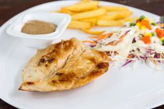 Grill chicken steak. Grill chicken steak and French Fries (potato chips), vegetable salad on a white plate Stock Images