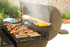 Grill. Chicken, white sausages and corn on the grill, smoke meat for cooking on coals, meat is located on the grill for cooking on the grill for coal, food, on Royalty Free Stock Images