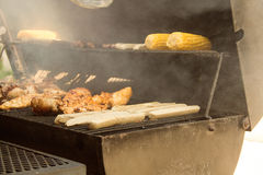 Grill. Chicken, white sausages and corn on the grill, smoke meat for cooking on coals, meat is located on the grill for cooking on the grill for coa Royalty Free Stock Images