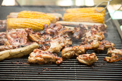 Grill. Chicken, white sausages and corn on the grill, smoke meat for cooking on coals, meat is located on the grill for cooking on the grill Stock Image
