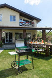 Grill with coals standing on green lawn and served table with dishes and drinks behind. Outdoor grill with coals standing on green lawn and served table with stock photos