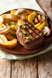 Grill fillet mignon with a garnish of potato wedges and mushroom. S close-up on a plate on a table. vertical Stock Photos