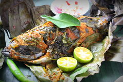 Grill Fish - Ikan Bakar. Ikan Bakar - Malaysian famous street food. Grill fish wrapped in banana leaf with a lots of spices Stock Image