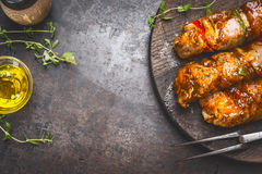 Grill food background with marinated skewers, meat fork, herbs spices and oil on dark rust metal background, top view royalty free stock image