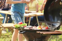 Grill with food and blurred people on background. Modern grill with food and blurred people on background Stock Photo