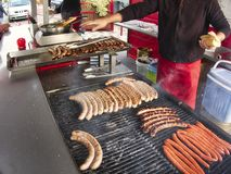 Grill frying fresh meat barbecue sausages, BBQ picnic sandwich store. Frying fresh meat barbecue sausages merguez brats, BBQ picnic sandwich store outdoor on big royalty free stock photo