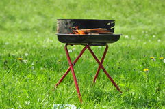 Grill on the grass. One grill in a middle of a field of green grass Stock Photography
