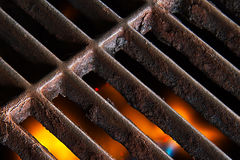 Grill Grate and Flames. A rusty grill grate with soft-focused flames below royalty free stock photography