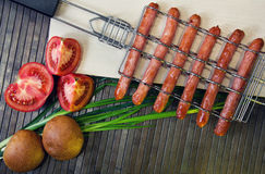 Grill-grate for sausages and tomato, bread, onions Royalty Free Stock Image